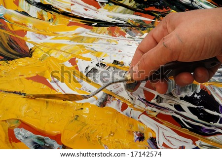 Woman hand painting in yellow  with spatula - stock photo