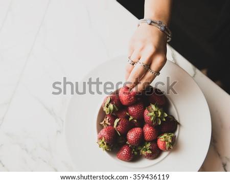 Woman hand picking some strawberries - stock photo