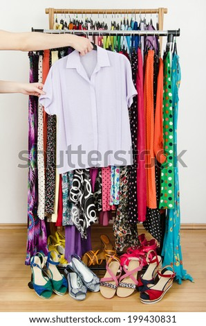 Woman hand picking up a purple shirt to wear. Summer dresses and sandals in a wardrobe. Dressing closet with colorful clothes and shoes nicely arranged on a rack. - stock photo