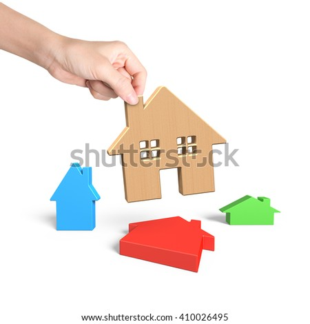 Woman hand picking wooden house, with three colorful small houses, isolated on white. - stock photo