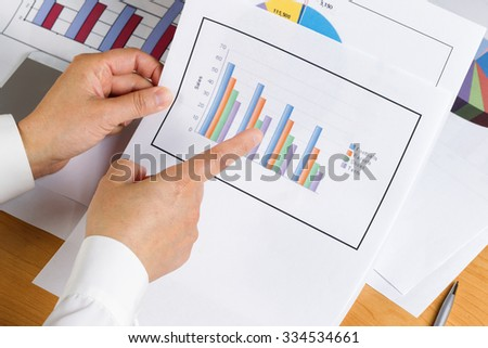 Woman hand pointing index finger at bar chart with printed graphs in background on desktop.