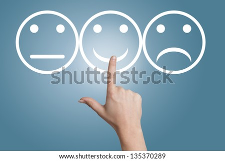 woman hand pointing to a smiling button on blue background