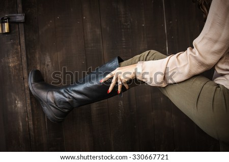 woman hand pull on black leather high flat boots on dark wooden background, closeup, outdoors, selective focus - stock photo