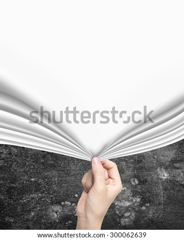 Woman hand pulling open new blank white curtain covering old mottled concrete wall. - stock photo