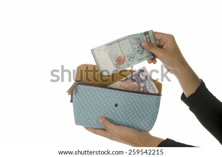 Woman hand put money in purse isolated on white background - stock photo