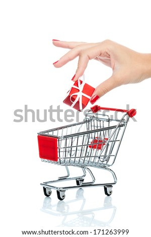 Woman hand putting down christmas present into shopping trolley isolated on white. Conceptual image - buying christmas presents.