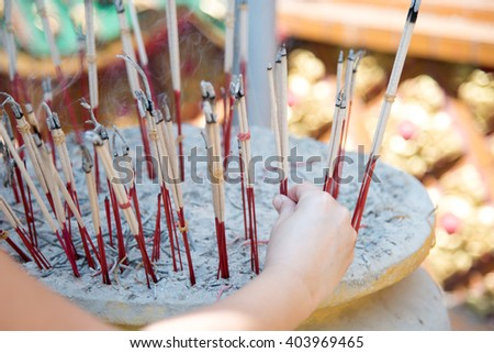 woman hand putting incense into Incense burner - stock photo