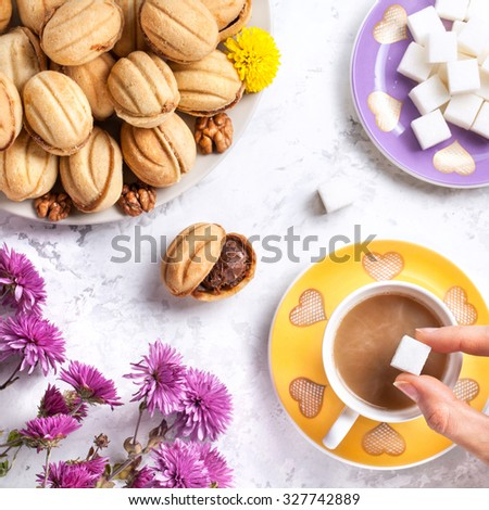 Woman hand putting sugar in coffee cup near sweet homemade nuts on white marble background   - stock photo