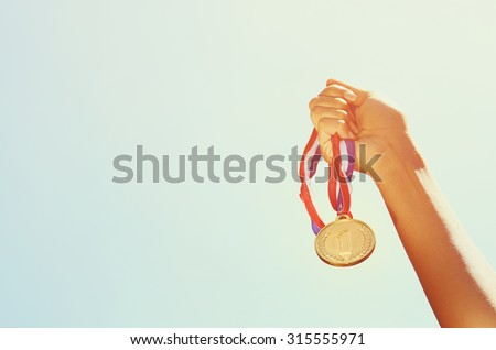 woman hand raised, holding gold medal against sky. award and victory concept - stock photo