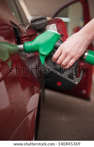 Woman hand refilling up gas tank of the car with green eco fuel on a filling station - stock photo
