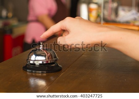woman hand ringing silver service bell on coffee shop