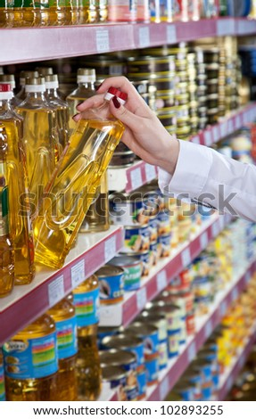 Woman hand selects the bottle of oil at the store - stock photo
