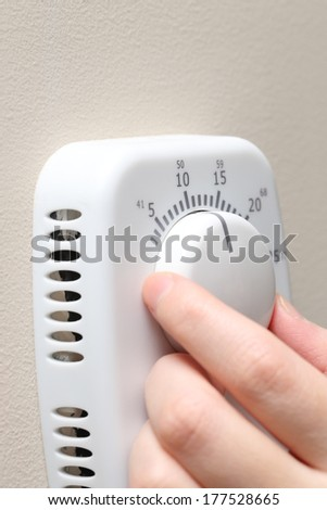Woman hand setting a thermostat  - stock photo