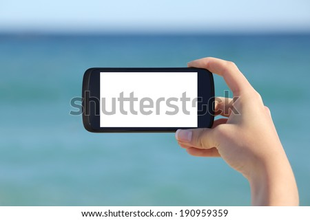 Woman hand showing a blank smart phone horizontal screen display on the beach with the sea in the background           - stock photo