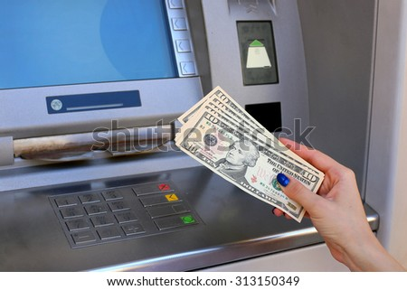 woman hand showing dollar banknotes in front of the atm - stock photo