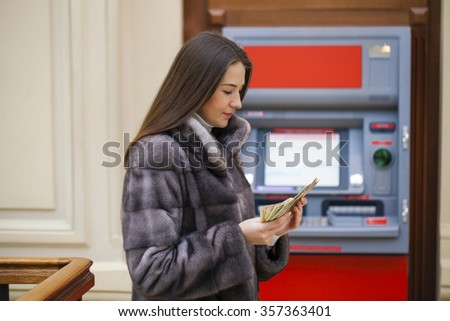 Woman hand showing dollar banknotes in front of the red atm - stock photo