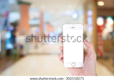 Woman hand showing smart phone with isolated screens display in a market or department store - stock photo