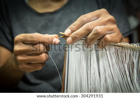 woman hand showing the golden thai silk - stock photo
