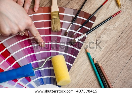Woman hand showing to sample color chart with tools on desk - stock photo