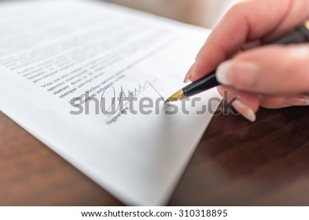 Woman hand signing a contract - stock photo