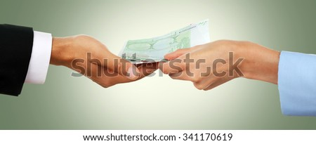 Woman hand takes money from the man's hand on green background