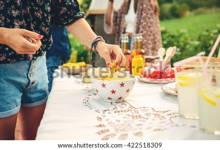 Woman hand taking chips potatoes from bowl - stock photo