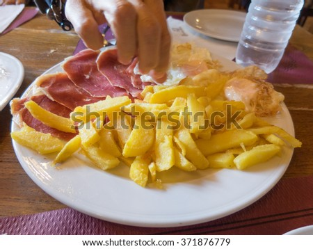 woman hand taking white dish with typical Spain food named huevos rotos or broken eggs with potatoes french fries fried eggs and slices of iberico iberian ham on table at cafe restaurant - stock photo