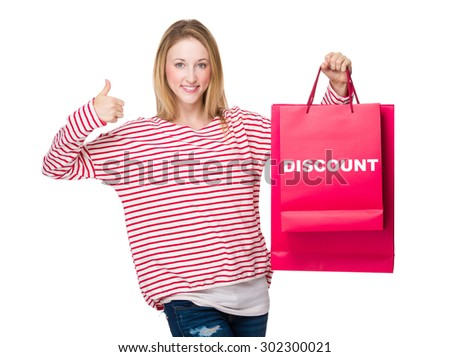 Woman hand thumb up gesture and hold with shopping bag showing discount - stock photo