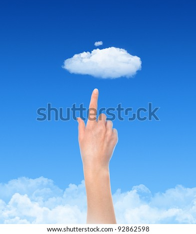 Woman hand touch the cloud against blue sky with clouds. Concept image on cloud computing and ecology theme with copy space.