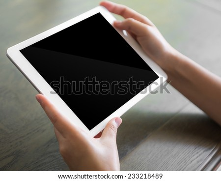 Woman hand touch white tablet with blank empty screen - stock photo