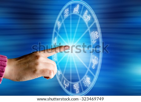 woman hand touching a zodiac chart with all signs - stock photo