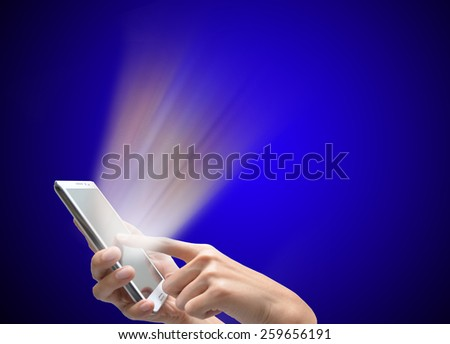 Woman hand touching mobile phone with colorful light shining