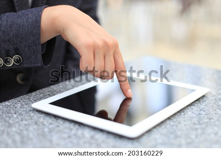 Woman hand touching screen on modern digital tablet pc. Close-up image with shallow depth of field focus on finger.