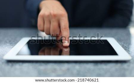 Woman hand touching screen on modern digital tablet pc. Close-up image with shallow depth of field focus on finger.  - stock photo