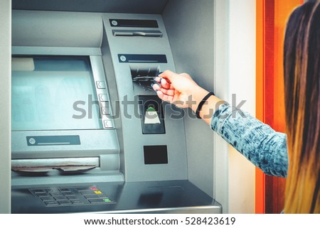 Woman hand using credit card to withdraw money from ATM