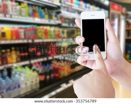 Woman hand using mobile phone while shopping in supermarket, online shopping concept - stock photo