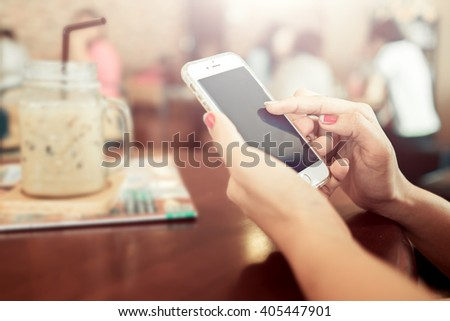 Woman hand using smart phone in coffee shop - stock photo