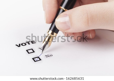 Woman hand voting no in check-box with blue fountain pen