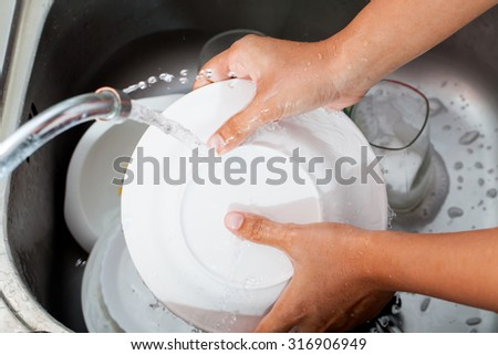Woman hand washing dishes over the sink in the kitchen - stock photo