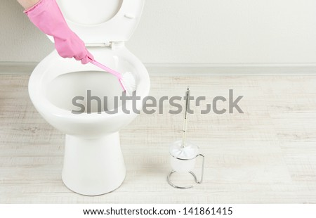 Woman hand with brush cleaning a toilet bowl in a bathroom - stock photo
