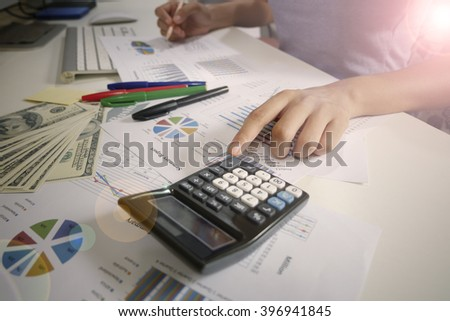 woman hand with calculator , graph and us dollar money ,  savings, finances, economy  concept , work at home concept , business concept ,business idea - stock photo