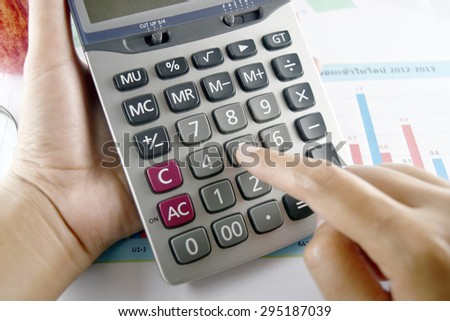 woman hand with calculator placed on document., concept for business