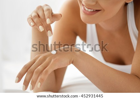 Woman Hand With Cream. Closeup Portrait Of Beautiful Happy Girl With Nude Makeup And Natural Manicure Nails Applying Cosmetic Moisturizing Hand Lotion On Soft Silky Skin. Beauty And Body Care Concept - stock photo