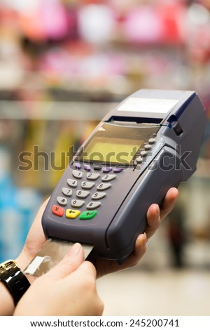 Woman hand with credit card swipe through terminal for sale in store - stock photo