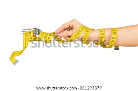 Woman hand with fork and measure tape isolated on white background - stock photo