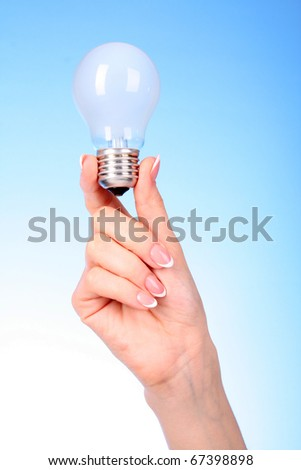 Woman hand with glow lamp on blue background - stock photo