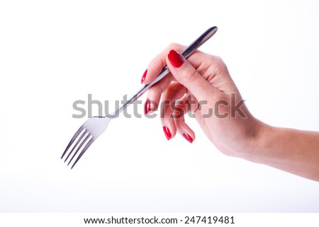 Woman hand with red manicure holding fork - stock photo