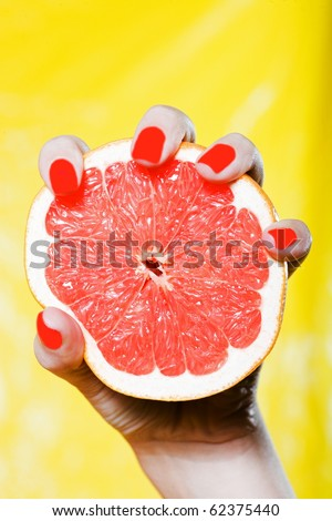 woman hand with red nails and colorful background squeezing grapefruit - stock photo