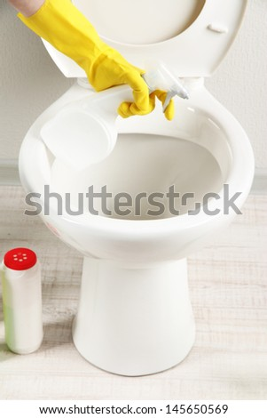 Woman hand with spray bottle cleaning a toilet bowl in a bathroom - stock photo