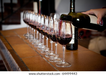 Woman hand with wine bottle pouring a row of glasses for tasting - stock photo